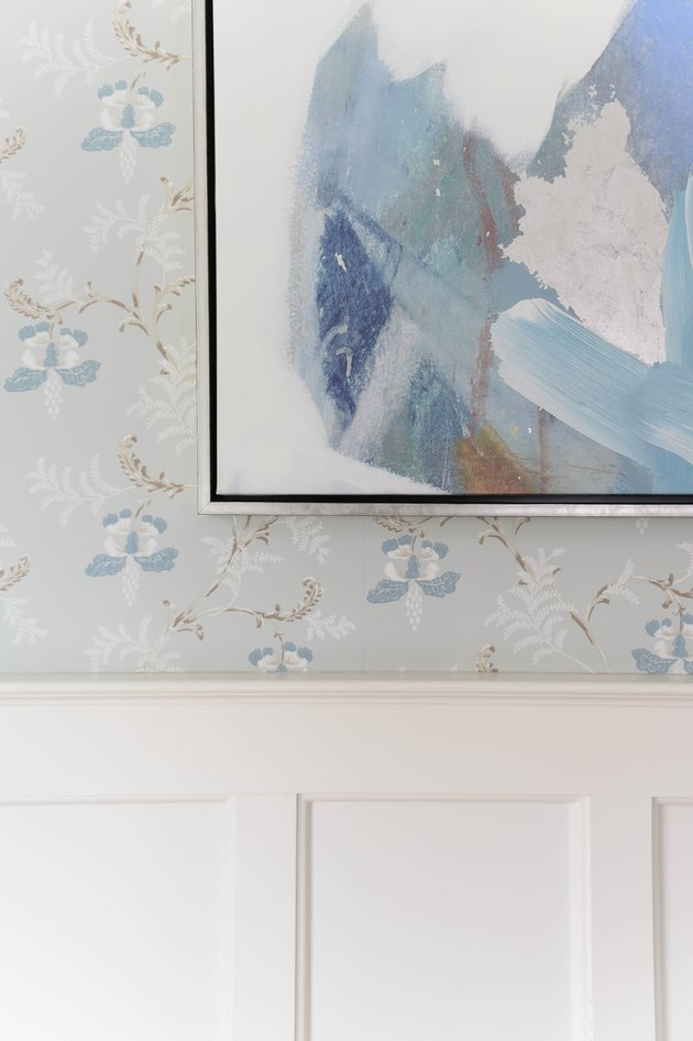 Modern artwork alongside blue and white floral wallpaper