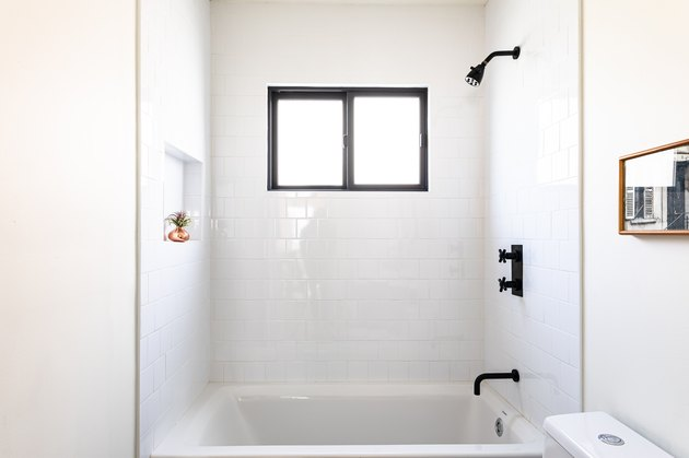 white bathroom with subway wall tile, black showerhead and faucets, white dual flush toilet