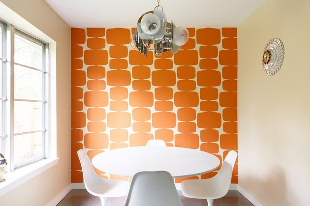 dining room space with orange wallpaper and table with chairs