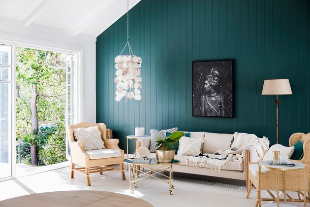 green living room idea with accent wall and rattan furniture