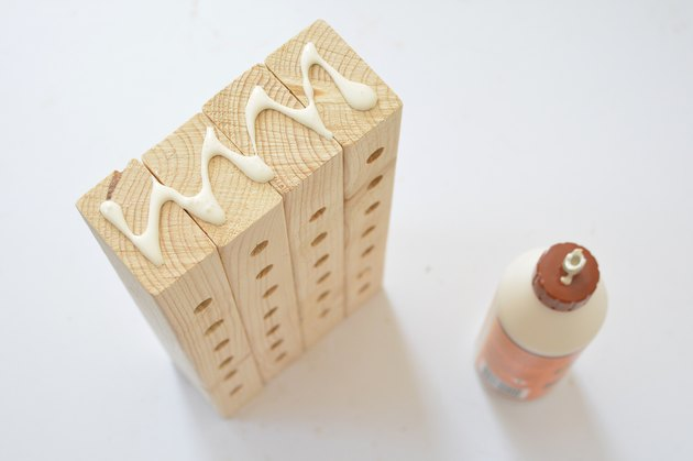 Applying glue along the top of the wooden bee house