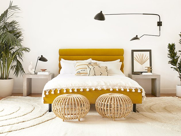 ochre color bed with white bedding and black wall sconce