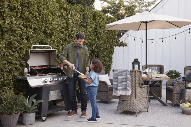 Father and daughter by grill outdoors
