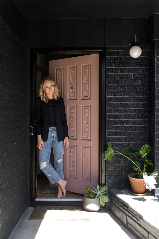 Kirsten Grove standing in front of front door and black brick wall with new Nest Hello System