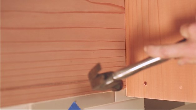 Hammering copper nails to redwood side board