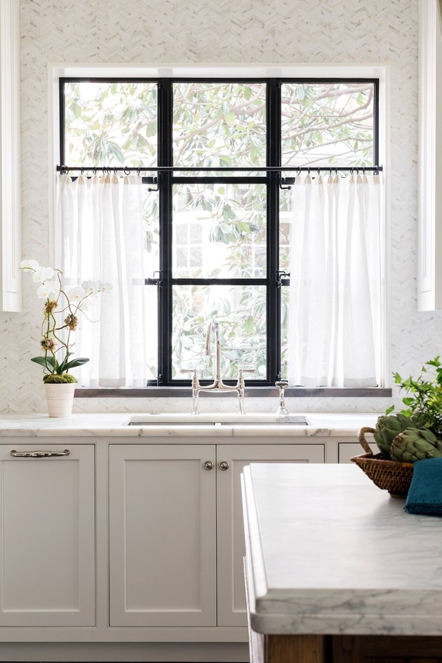 Modern kitchen window with half curtains and marble island