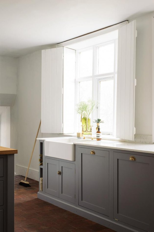 Farmhouse kitchen window with tall shutters and gray cabinets