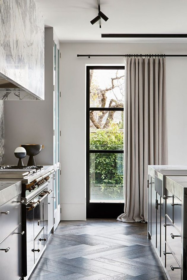 Contemporary kitchen window with gray drapes and black window panes