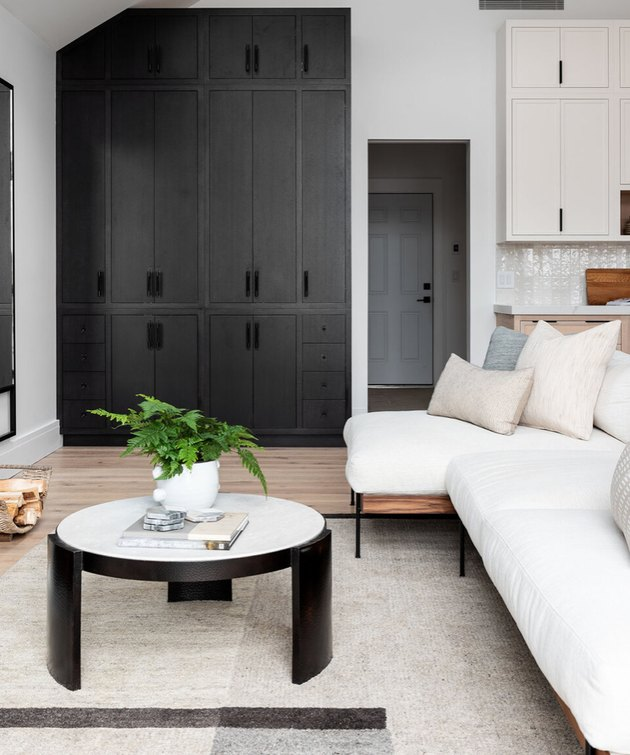 basement storage ideas with black built-in cabinets, white sectional couch, throw pillows, white and black round coffee table, geometric rug.