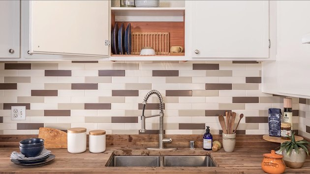 kitchen sink, wood countertop, open cabinet, patterned tile backsplash