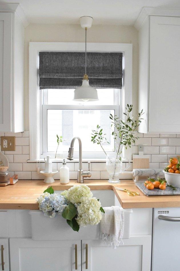 Farmhouse kitchen window with gray roman shades