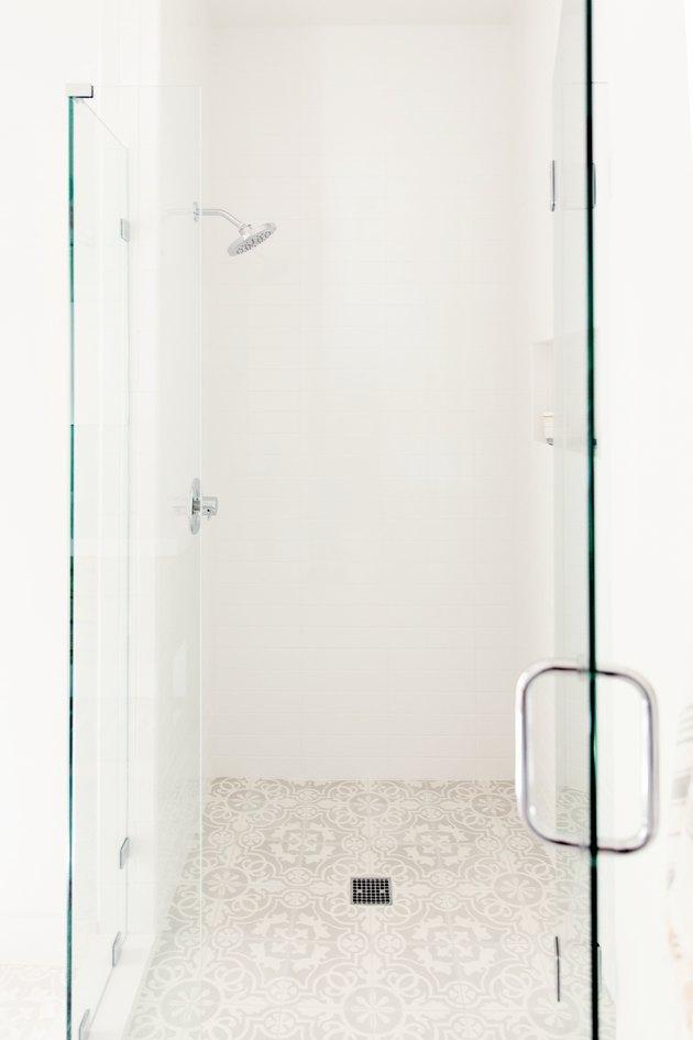 glass shower door, tan patterned shower floor tile, black shower drain, silver shower head, silver shower handle