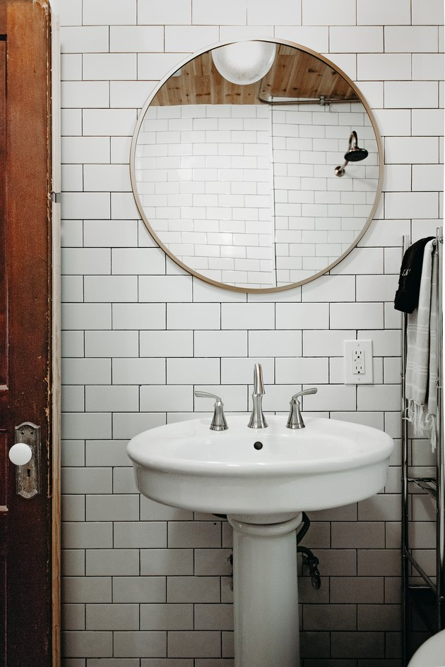 white ceramic pedestal sink, round mirror, white subway tile wall