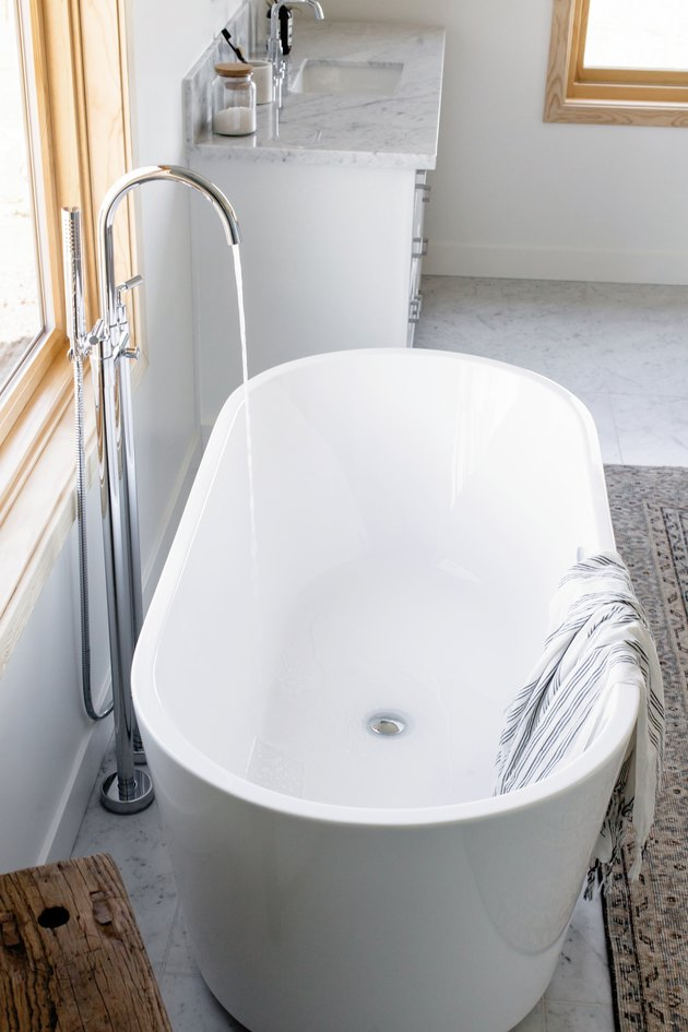 white freestanding tub with water flowing from floor-mount silver faucet, striped towel draped over the side, area rug, bathroom vanity with marble counters
