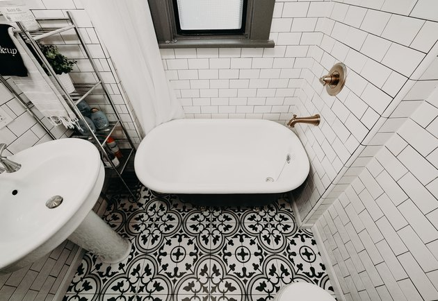 black and white tile patterned floor, freestanding black and white clawfoot tub, white subway tile wall, bronze wall-mount faucet, white pedestal sink
