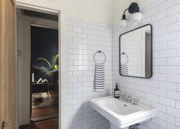 white pedestal sink, white subway tile wall, rectangular mirror with black trim, black light fixture, striped towel hung up, door leading to hallway with wood floors