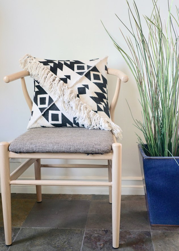 DIY Fringe Pillow Out of a Rug on wishbone chair.