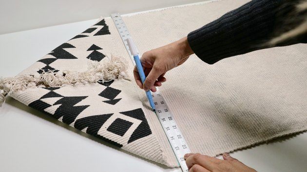 Marking a cut line on a rug for DIY Fringe Pillow Out of a Rug project