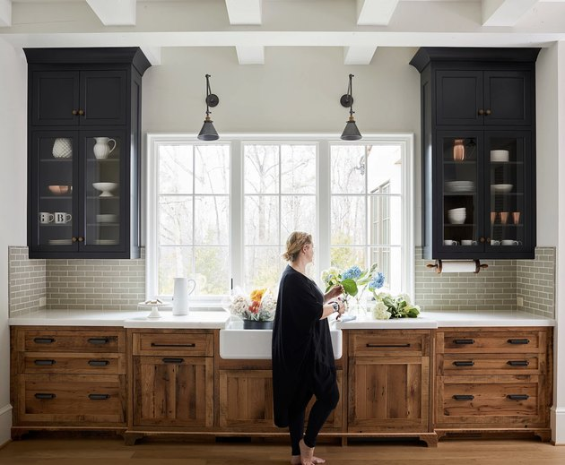 black kitchen cabinet idea with rustic wooden lower cabinets with white countertops and a white farmhouse sink. Above the counter on either side of a large window are two black cabinets with glass doors.