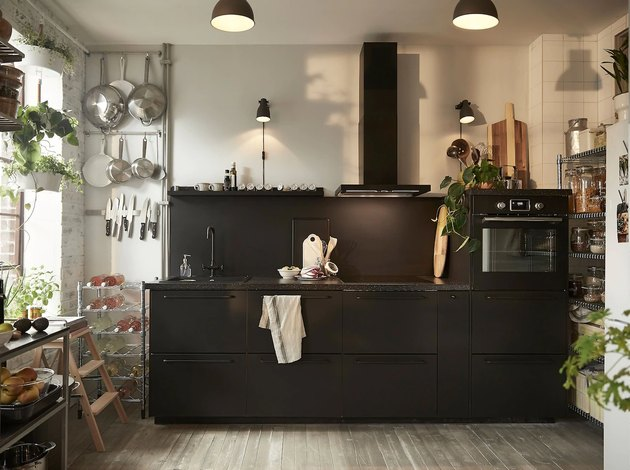 black kitchen cabinet idea for an industrial loft kitchen with black lower cabinets, a black blacksplash, and a black range hood