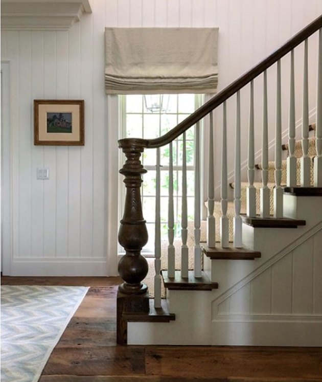 traditional staircase with wood railing and white spindles