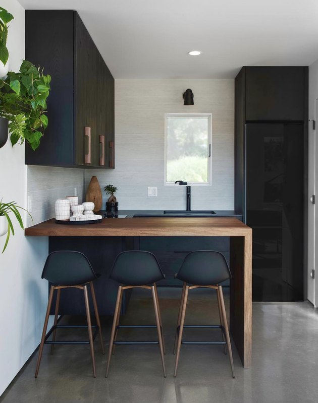black kitchen cabinet idea for a small modern kitchen with matte black cabinets and a walnut waterfall countertop