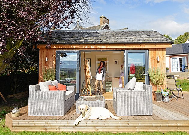 modern she shed in backyard wood deck and outdoor seating