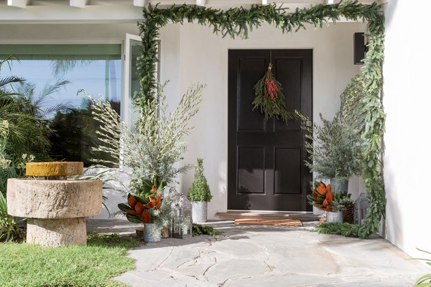 black traditional front doors with green garland and potted plants