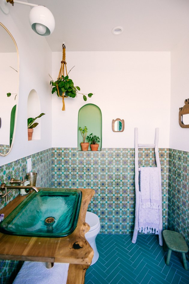 bathroom backsplash idea with green patterned tile wainscoting and chevron tile floor