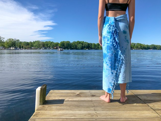 Woman wrapped in tie-dye towel by lake