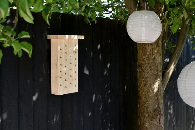 Bee house hanging on black garden fence