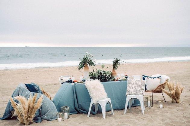 A table with light blue tablecloth on a beach