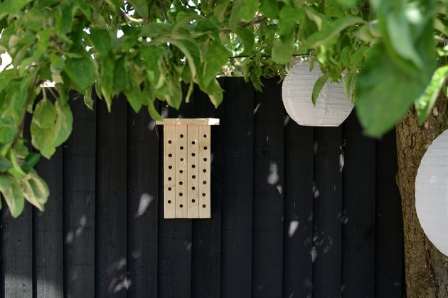 Wooden bee house on black garden fence
