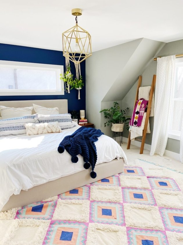 cream carpet colors in bohemian bedroom with patterned rug and blue accent wall