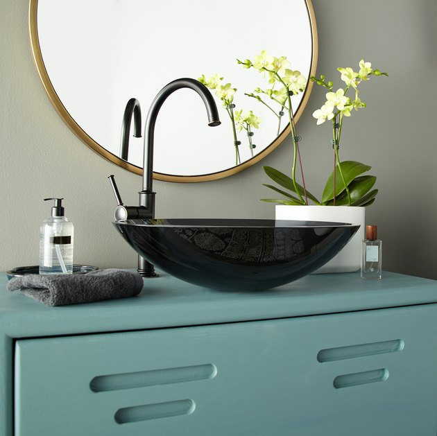 bathroom with black sink and blue cabinet