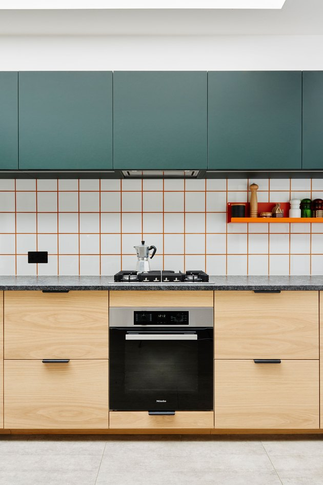 white tile kitchen backsplash with orange grout with green upper cabinets