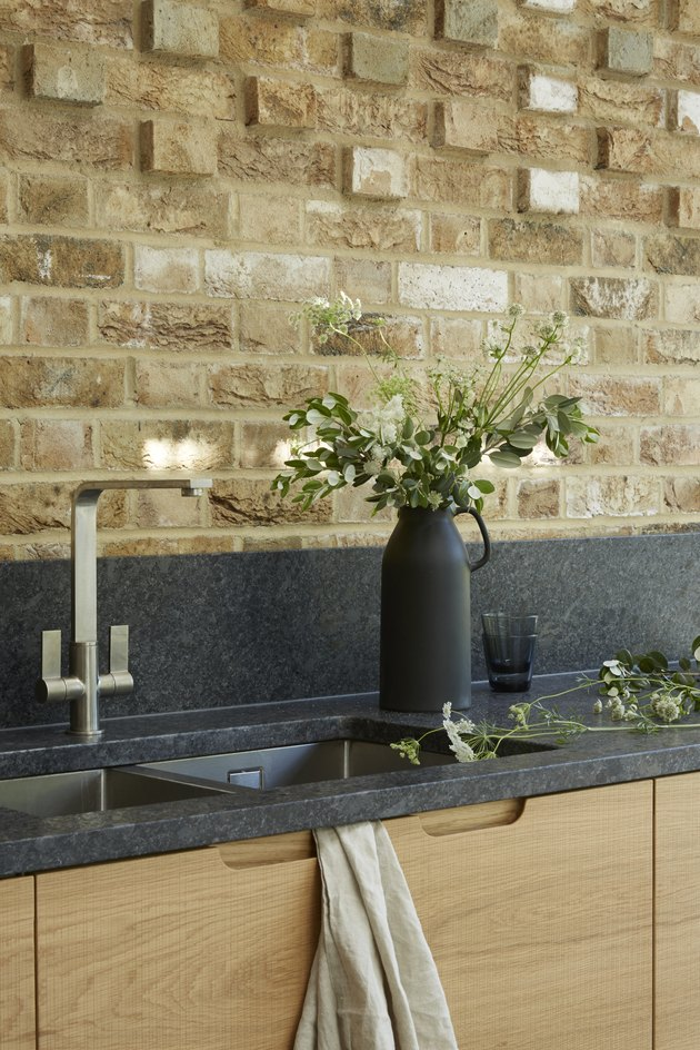 black kitchen backsplash  backsplash and black countertops with wood cabinets and brick wall