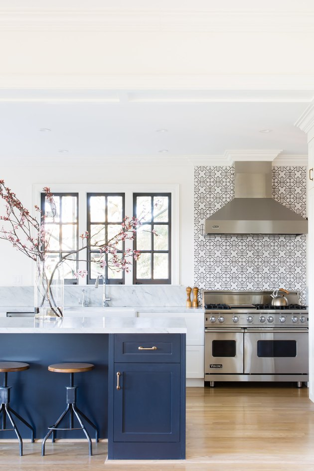 modern kitchen backsplash idea in light and bright space with blue cabinets and marble countertops
