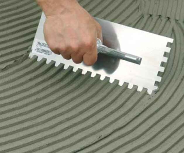 Spreading adhesive with a notched trowel.