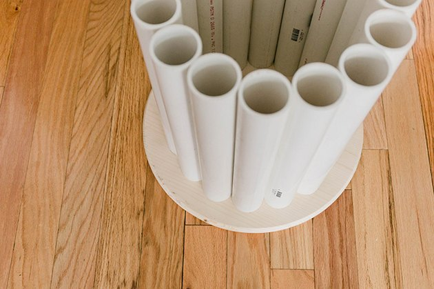 Lay the cut pipes out in a circle around the underside of the wood tabletop.