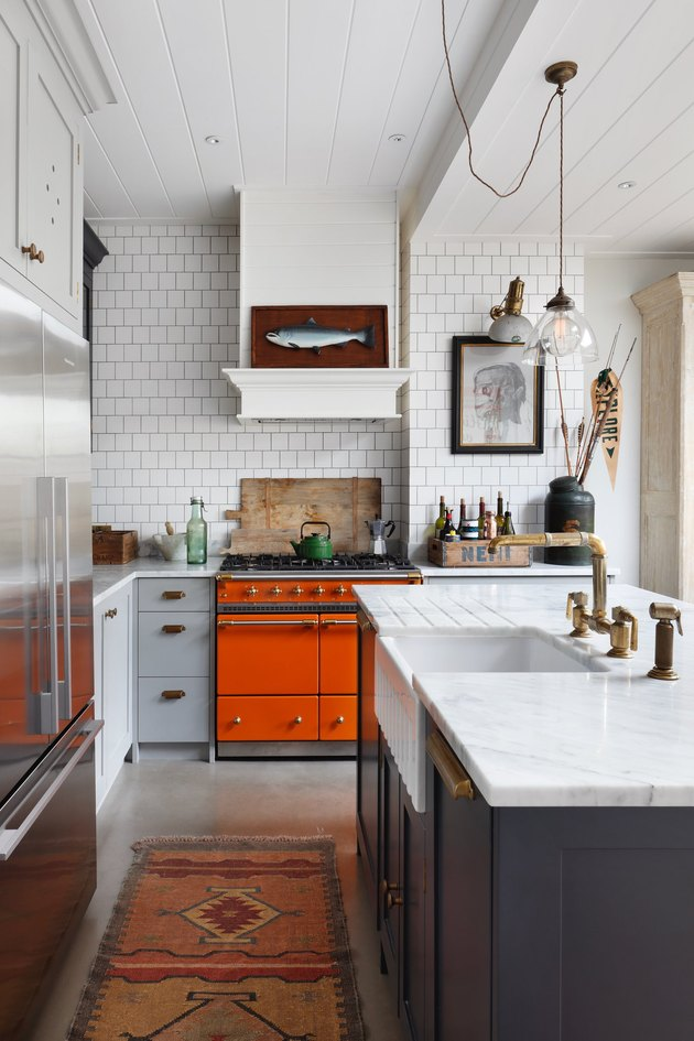 white midcentury modern kitchen backsplash idea with tile backsplash and orange oven