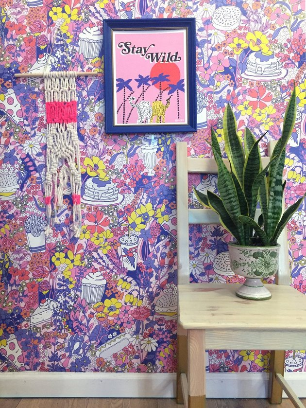 colorful wallpaper with a wall hanging, framed print, chair and plant nearby