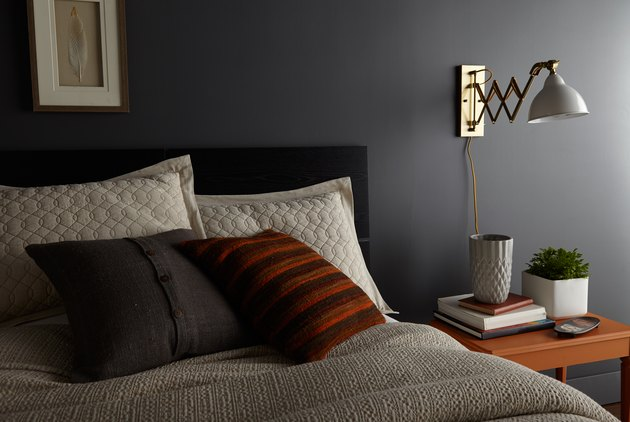 bedroom space with charcoal gray wall