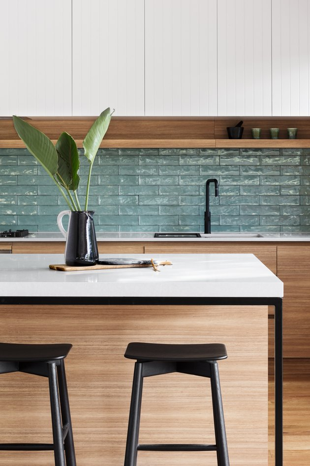 green textured kitchen backsplash with wood cabinetry and whit countertops