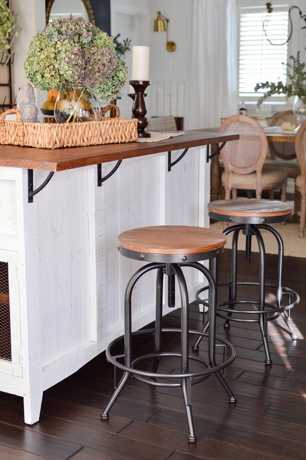 Industrial farmhouse kitchen with white island and metal bar stools