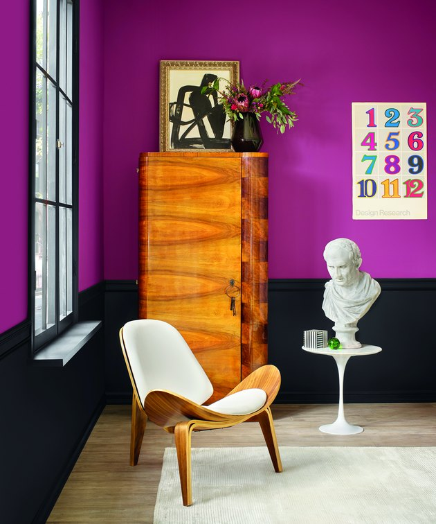 room with chair, dresser, sculpture, and magenta wall