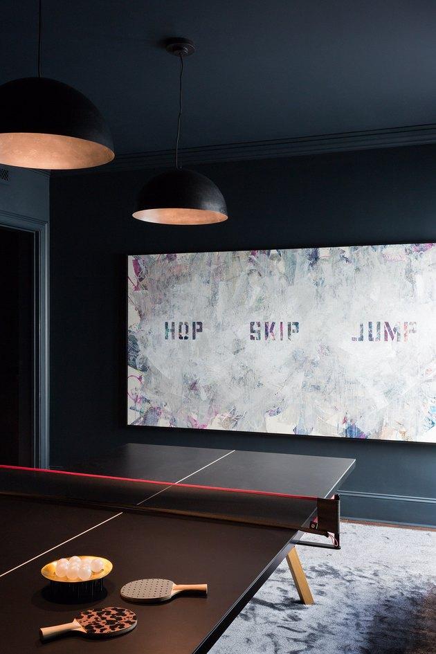 attic game room with dark brown ping pong table, dark gray walls, modern art, black pendant lamps, gray rug.