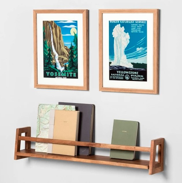 bookshelf with books and two printed frames