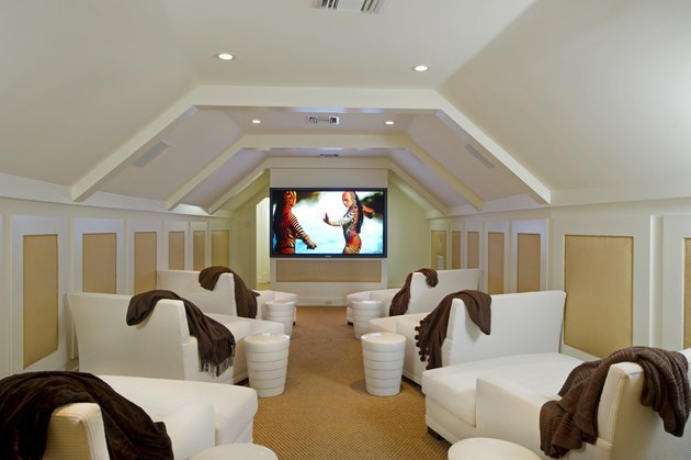 attic game room with white chaise loungers, yellow and white walls, big screen tv, white end tables, brown throws.