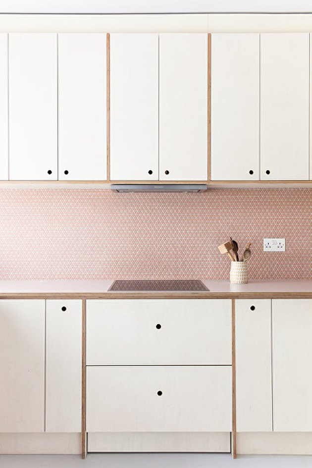 white kitchen cabinetry with pink mosaic kitchen backsplash